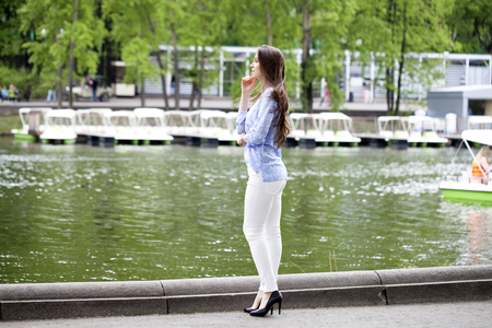 Happy young woman in white pants and a blue shirt walking in the summer park photo
