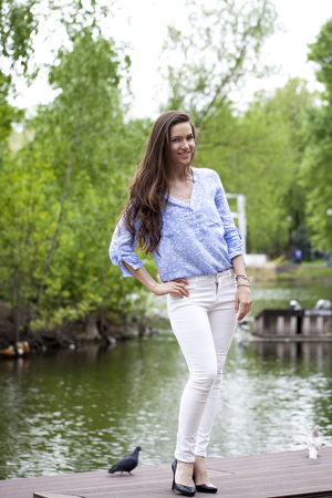 white pants: Happy young woman in white pants and a blue shirt walking in the summer park