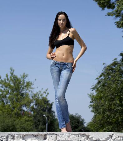 simbolo de la mujer: Alto, delgado modelo en vaqueros en el fondo de cielo azul