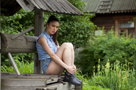 stair well: Young beautiful girl sits on a wooden pit in the park