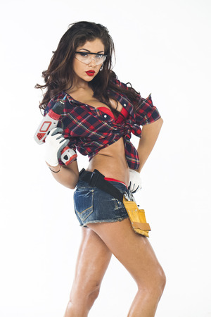 High fashion glamour model in Daisy duke shorts, tool belt, red bra with a screw gun  Stok Fotoğraf