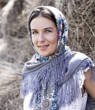 Portrait of young happy woman in blue scarf photo