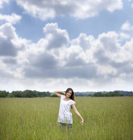 Happy young woman walks in summer field photo