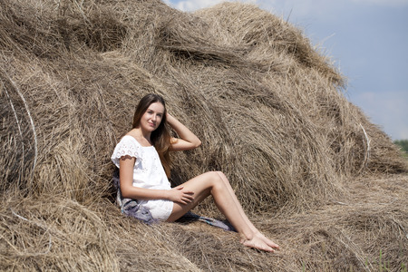 Young beautiful girl in the hayloft in the village photo