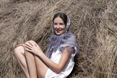 haymaking: Portrait of young happy woman in blue scarf