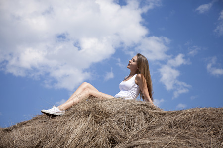 haymaking: Young beautiful girl in the hayloft in the village