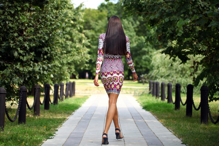 walk away: Sexy young brunette walking in summer park Stock Photo
