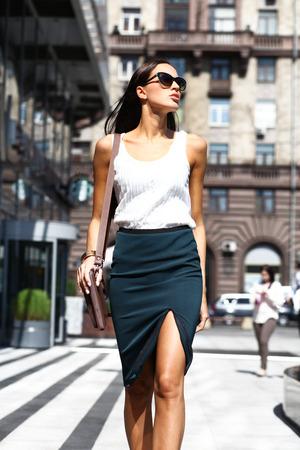 Jonge mooie brunette vrouw met een tas in zijn hand