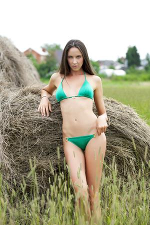 hayloft: Modelo hermosa joven en un bikini verde en el pajar Foto de archivo