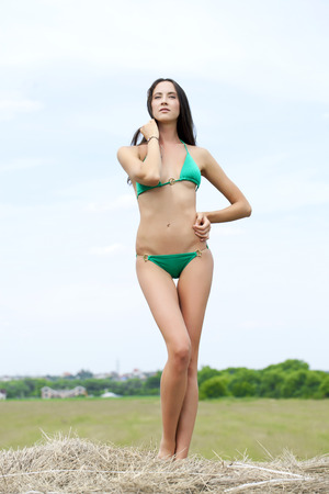 hayloft: Young beautiful model in a green bikini in the hayloft Stock Photo