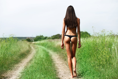 russian: Young beautiful model in black bathing suit walking in the summer field