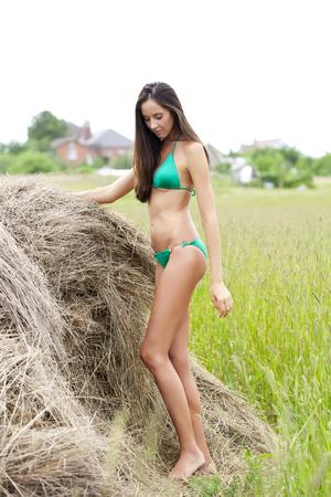 hayloft: Young beautiful model in a green bikini in the hayloft Stock Photo