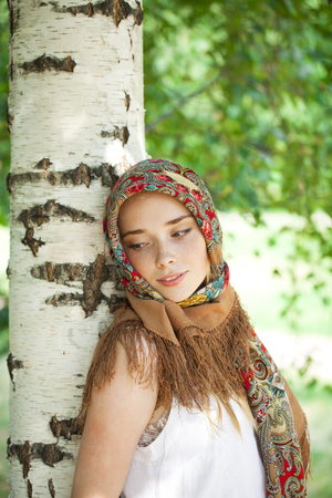 Russian beauty woman in the national patterned scarf photo