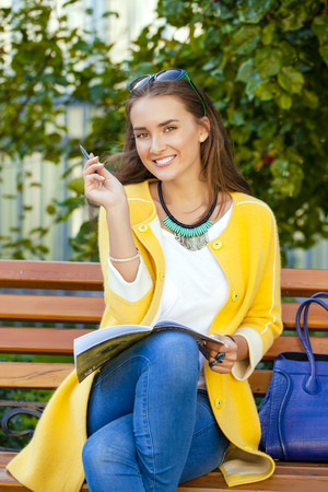 Happy young brunette sitting on a park bench photo