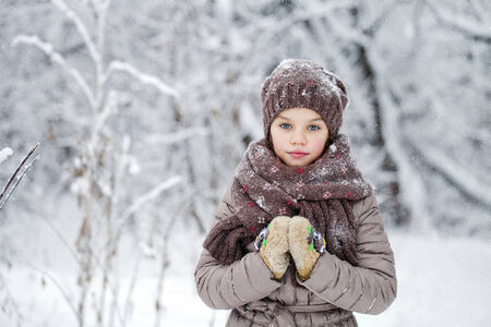 Close-up portrait of a little girl in brown jacket and knit scarf and hat on a background of a snow park photo