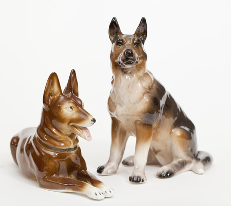 adeptness: German Shepherds. Ceramic figurine, dog breed isolated on white