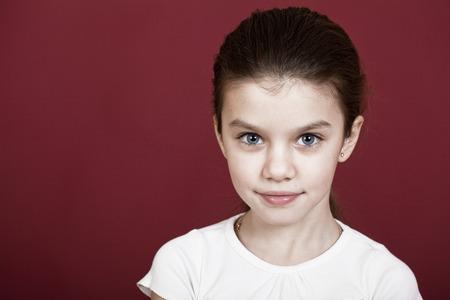 burgundy background: studio portrait of a pretty little girl on a burgundy background Stock Photo