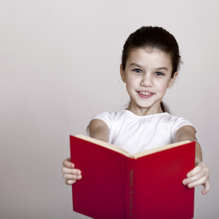 red book: Little girl holding red book, studio on white background