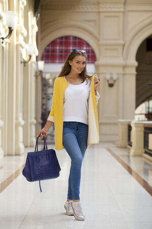 go inside: Beautiful young woman in yellow coat walking in the shop