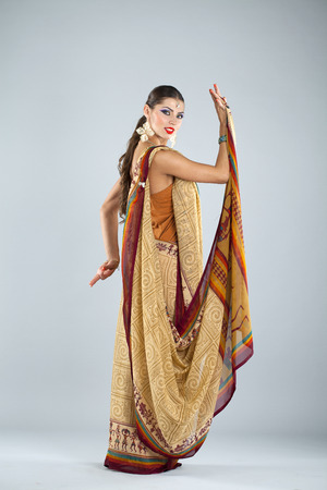 pakistani ethnicity: Full body cheerful traditional Asian Indian woman in indian sari, isolated on gray background