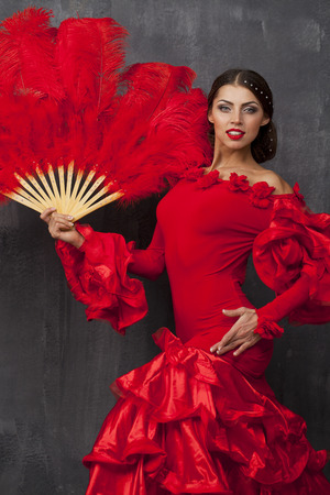 flamenco dress: Sexy Woman traditional Spanish Flamenco dancer dancing in a red dress with fan Stock Photo