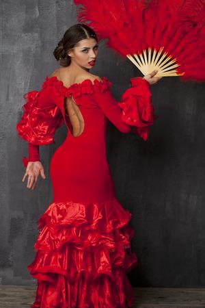 Sexy Mujer tradicional bailarín baile flamenco español en un vestido rojo con ventilador