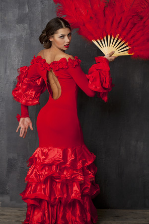 Sexy Woman traditional Spanish Flamenco dancer dancing in a red dress with fan Stock Photo