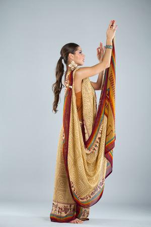 mujer cuerpo entero: Alegre todo el cuerpo de la mujer india tradicional asi�tica en sari indio, aislado sobre fondo gris Foto de archivo