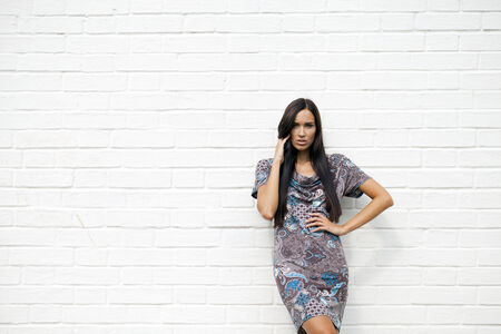 colorful dress: Beautiful young woman in colorful dress, against white wall Stock Photo