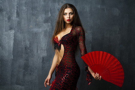 Sexy Woman traditional Spanish Flamenco dancer dancing in a red dress with fan Stok Fotoğraf