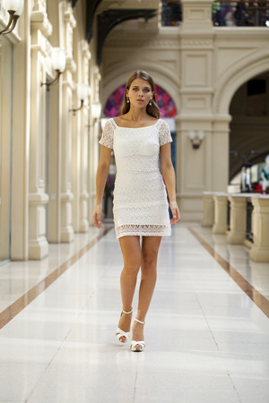 go inside: Beautiful young woman in white dress walking in the shop