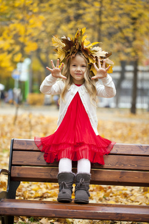Beautiful little girl sitting on a bench in autumn park photo