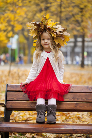 little girl sitting: Beautiful little girl sitting on a bench in autumn park Stock Photo