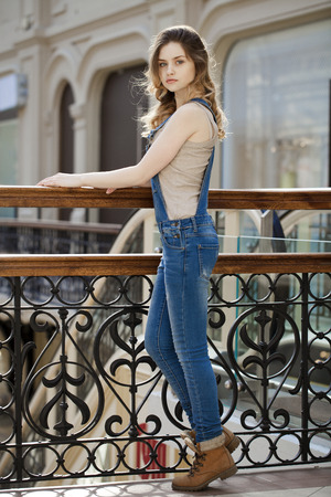 girl in full growth: Portrait in full growth the young girl in denim overalls Stock Photo