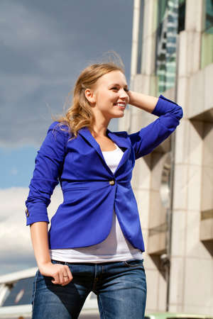 Beautiful young blonde in a blue jacket, portrait outdoors photo