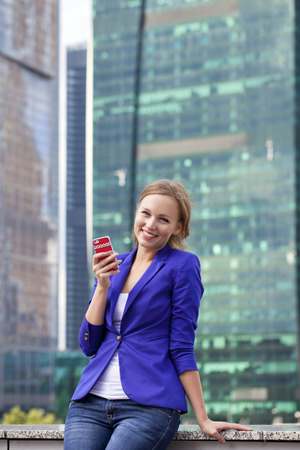 Beautiful young blonde in a blue jacket calling by phone photo