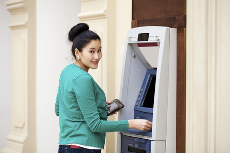automated teller: Asian lady using an automated teller machine . Woman withdrawing money or checking account balance Stock Photo