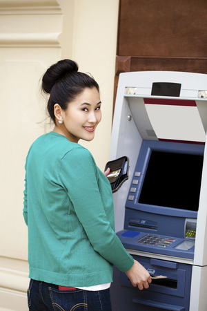 checking account: Asian lady using an automated teller machine . Woman withdrawing money or checking account balance Stock Photo