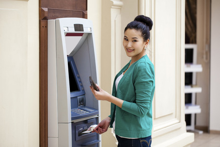 Asian lady using an automated teller machine . Woman withdrawing money or checking account balance Stock Photo