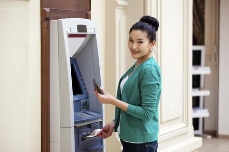 cuenta bancaria: Señora asiática que usa un cajero automático. Mujer que retira el dinero o saldo de la cuenta de cheques