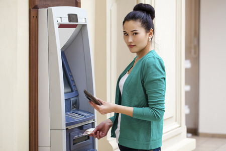 Asian lady using an automated teller machine . Woman withdrawing money or checking account balance photo