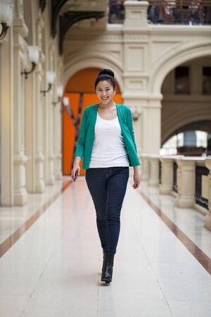 go inside: Beautiful young asian woman in green blouse walking in the shop Stock Photo