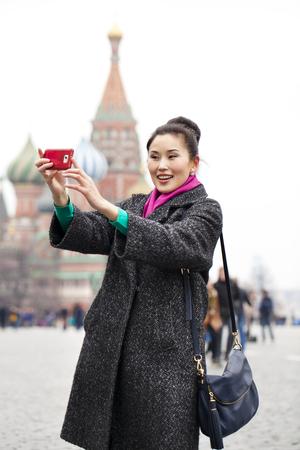 red square moscow: Joven que toma la mujer tur�stica im�genes hermosas en el tel�fono m�vil en el fondo de la Plaza Roja, el Kremlin de Mosc�, Rusia Foto de archivo