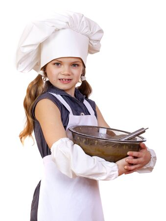Little girl cook whips whisk eggs in a large plate, isolated on white background photo