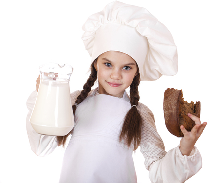 Cooking and people concept - Little girl in a white apron holding a jug of milk, isolated on white background photo