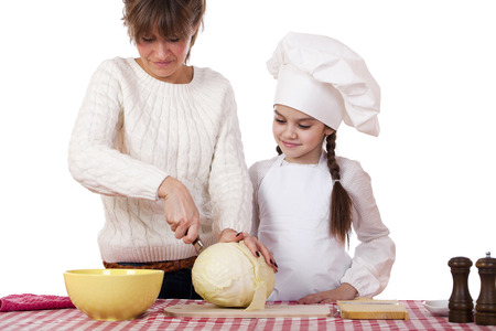 Cooking and people concept - Little girl in cook hat and mother, isolated on white background photo