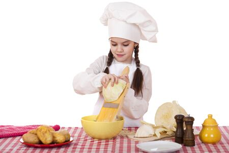 shred: Portrait of a little girl in a white apron and chefs hat shred cabbage in the kitchen, isolated on white background Stock Photo