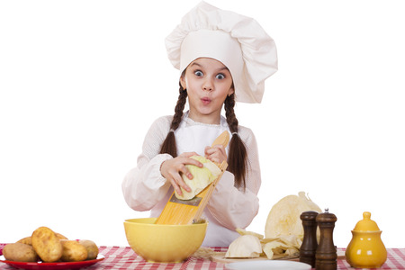 little girl smiling: Portrait of a little girl in a white apron and chefs hat shred cabbage in the kitchen, isolated on white background Stock Photo