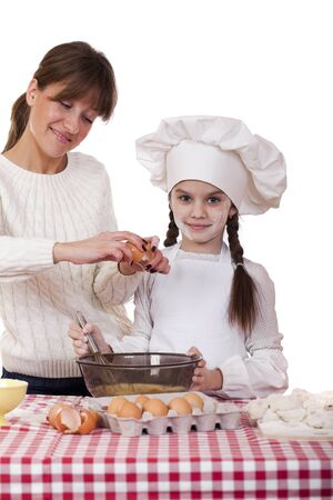 Happy mother with little daughter joyful cooking, isolated on white background photo