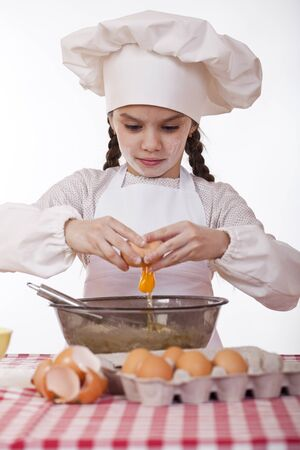 breaks: Little cook girl in a white apron breaks eggs in a deep dish, isolated on white background